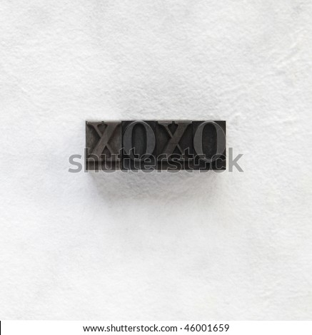 XOXO in old metal type on handmade paper - stock photo