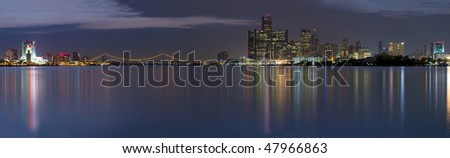 XXL Panoramic of the Detroit Windsor skyline with the Ambassador Bridge connecting the United States with Canada.  Night shot with city lights reflecting in the Detroit River. - stock photo