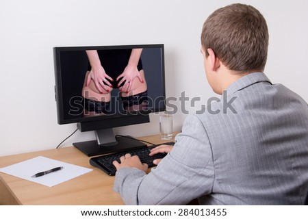 xxx concept - young business man looking adult content at work - stock photo