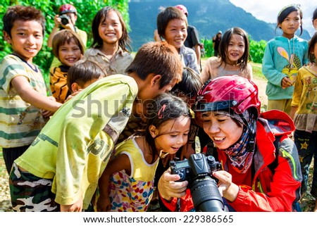 Y TY, LAOCAI, VIETNAM - SEPTEMBER 6, 2014 - Ethnic children gathering to see their photos taken by an unidentified photographer nearby the rice terraces. The children are very friendly with tourists.  - stock photo