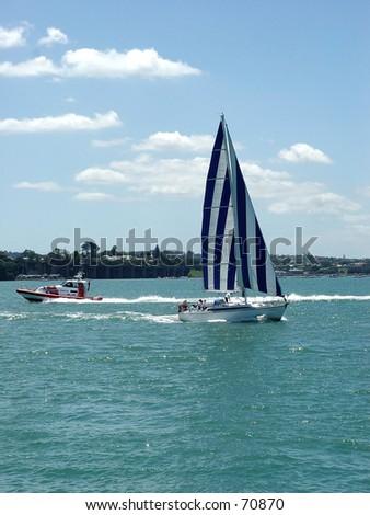 Yacht and coastguard boat in Auckland New Zealand - stock photo