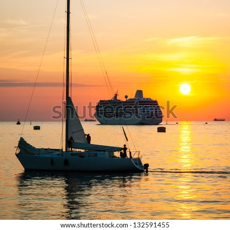 Yacht and cruise ship sailing against sunset. Holiday lifestyle landscape with skyline sailboat. Sea tourism - maritime evening walk. Romantic trip during the sea sunset. - stock photo