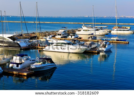 yacht and motorboats on blue water, beautiful marina view - stock photo