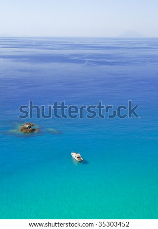 Yacht approaching a small island on azure sea with volcanic island of Stromboli on the horizon
