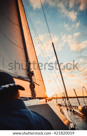 yacht at sunset and diffuse back man - stock photo
