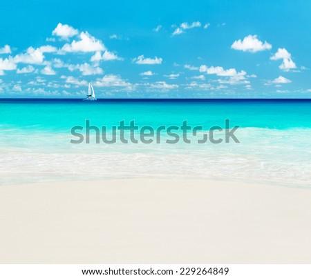 Yacht at tropical ocean beach. Anse Georgette, Praslin island, Seychelles - vacation background - stock photo