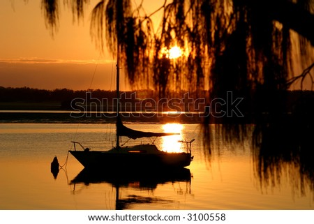 Yacht bathed in early morning golden light. - stock photo