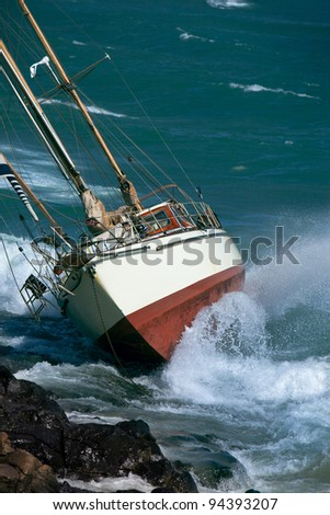 yacht crash on the rocks in stormy weather - stock photo