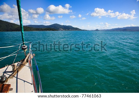 yacht deck with sail navigates towards island at open sea aquatic sunny beautiful day with blue sky - stock photo