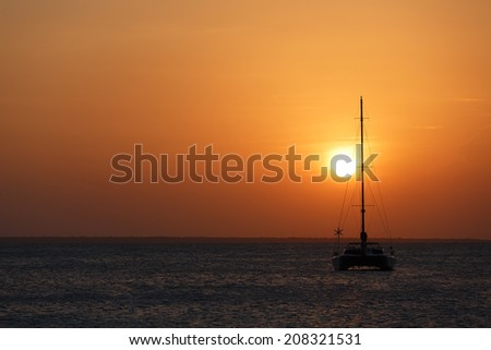 Yacht during sunset on the ocean - stock photo