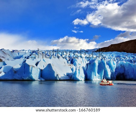 Yacht for tourists near the magnificent Glacier Grey Lake Grey. Sunny and windy summer day in the national park Torres del Paine. Patagonia, Chile - stock photo