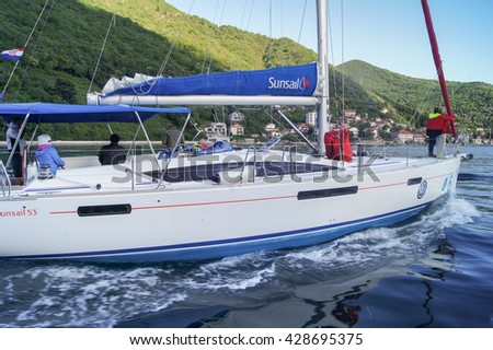 """Yacht going to the motor without a sail. Tivat, Montenegro - 26 April, 2016. Regatta """"Russian stream"""" in God-Katorskaya bay of the Adriatic Sea off the coast of Montenegro. - stock photo"""