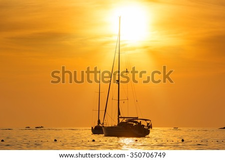 Yacht in the sea at sunset hot yellow light - seascape background - stock photo