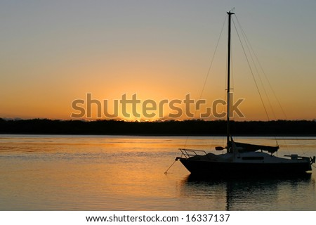Yacht moored at peace in the early morning dawn light. - stock photo