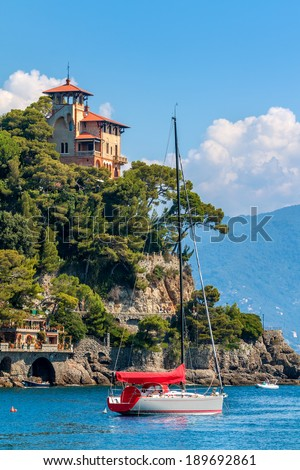 Yacht on the sea and beautiful old villa on the cliff in Portofino, Italy (vertical composition). - stock photo