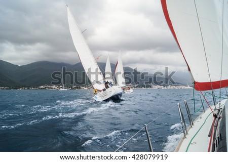 "Yacht Regatta under a cloudy sky. Tivat, Montenegro - 28 April, 2016 Regatta ""Russian stream"" in God-Katorskaya bay of the Adriatic Sea off the coast of Montenegro. - stock photo"