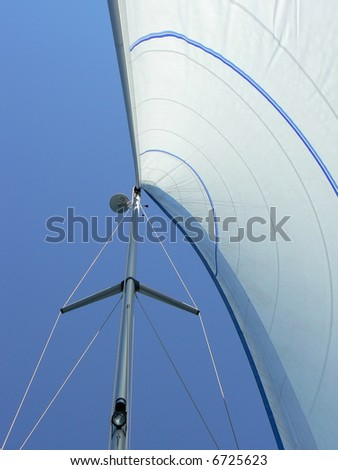 Yacht sail and mast with blue cloudless sky in the background. Vertical perspective. - stock photo