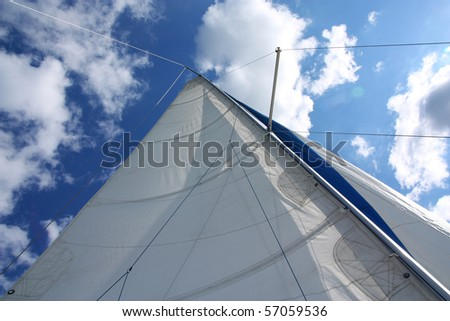 Yacht sail and mast with white cloudless and blue sky in the background - stock photo