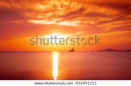 Yacht sailing against full Red sunset. Holiday lifestyle landscape with skyline.  - stock photo