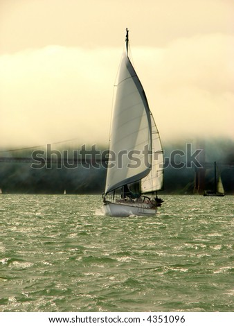 Yacht sailing in San Francisco Bay with the Golden Gate Bridge in the background, on foggy day - stock photo