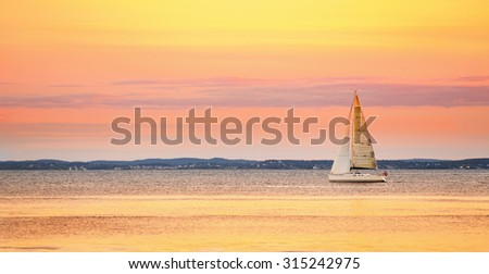 Yacht sailing in the sea at sunset - stock photo