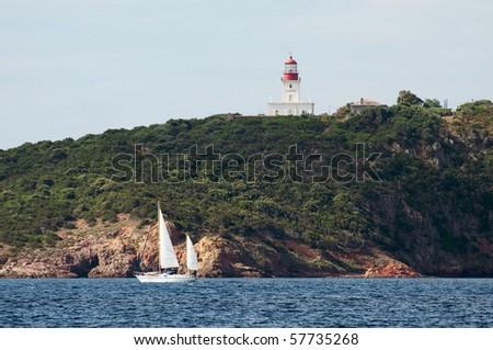 yacht sailing near La Chiappa lighthouse close to Porto Vecchio, Corsica - France - stock photo