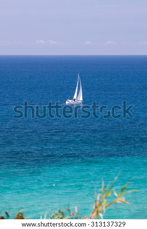 Yacht sailing off the coast in tropical waters - stock photo