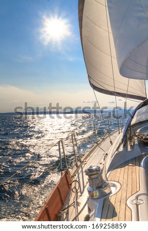 Yacht sailing towards sunset on blue sea - stock photo