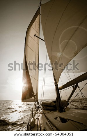 yacht sailing towards sunset - picture in sepia tone - stock photo