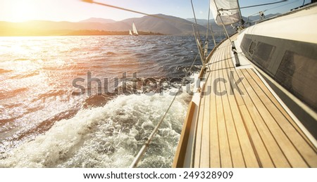Yacht sailing towards the sunset. - stock photo