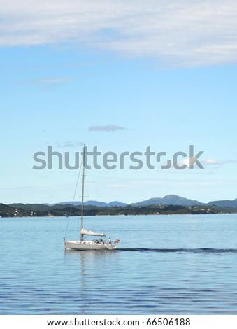 Yacht sailinng past Norway coastline near the Bergen - stock photo