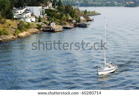 Yacht sailinng past Sweden coastline - stock photo