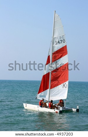 Yacht with sportsmen in the dark blue sea - stock photo