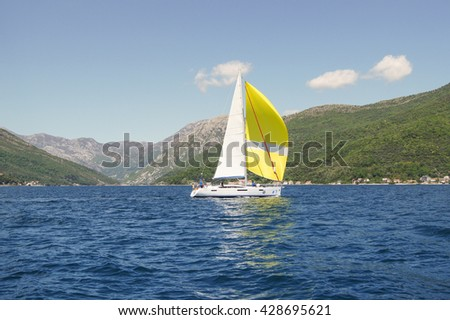 """Yacht with white and yellow sail. Tivat, Montenegro - 26 April, 2016. Regatta """"Russian stream"""" in God-Katorskaya bay of the Adriatic Sea off the coast of Montenegro. - stock photo"""