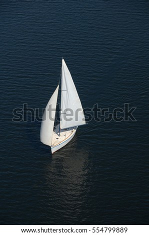 yacht with white sails on the blue surface of the water, top view