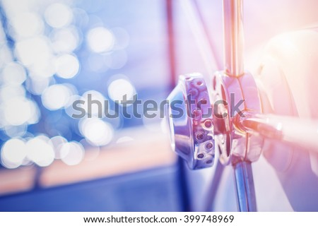 Yachting detail - Rudder on deck / board with water and sun reflection in background. - stock photo