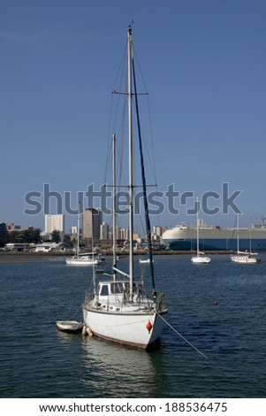 Yachts anchored at yacht mole in harbor against Durban City Skyline in South Africa - stock photo