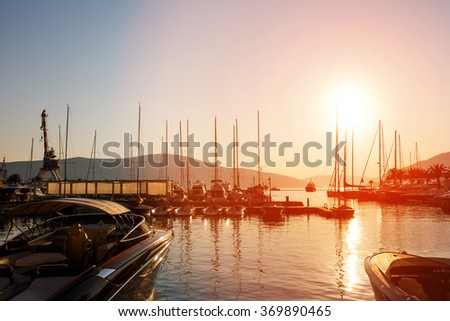 Yachts and boats at Adriatic sea bay at sunset in golden and pink tones. Porto Montenegro, Tivat - stock photo