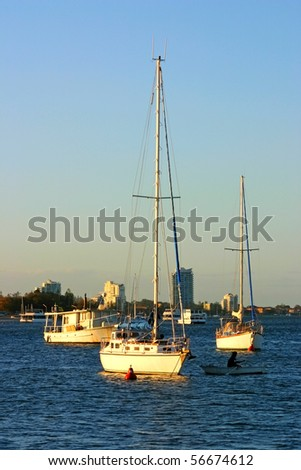 Yachts and boats at anchor in the setting sun at the end of the day. - stock photo