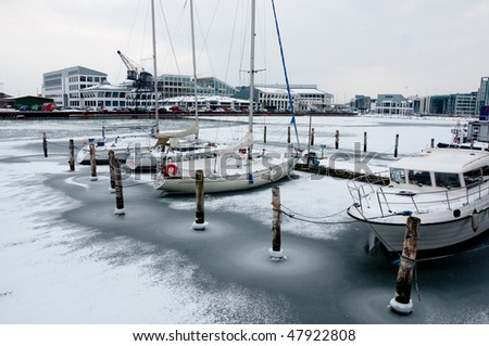 Yachts and boats, loaded with snow, waiting for the summer at frozen port - stock photo