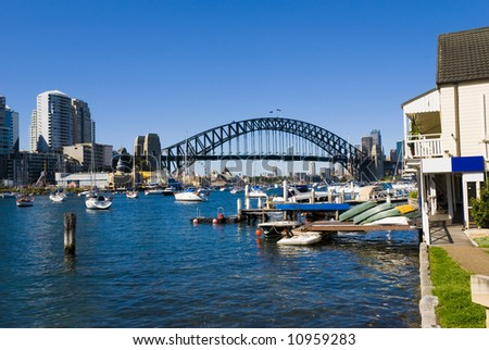Yachts and boats on Sydney Harbour ( harbor ) with the Bridge and Opera House in the background on a perfect blue sky day