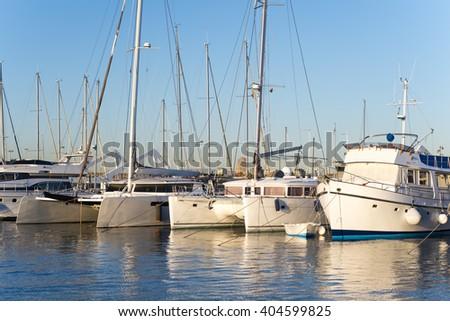 Yachts and sailboats moored in marina. Summertime vacation , sunrise  - stock photo