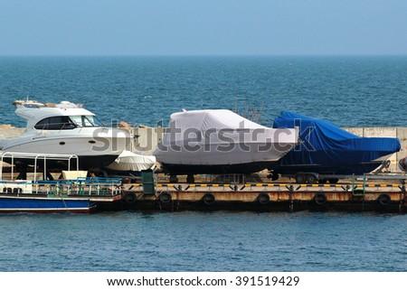 yachts ashore in a boatyard - stock photo