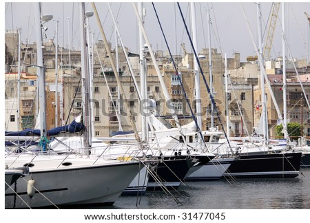 yachts berthed at a marina in malta on an overcast day - stock photo