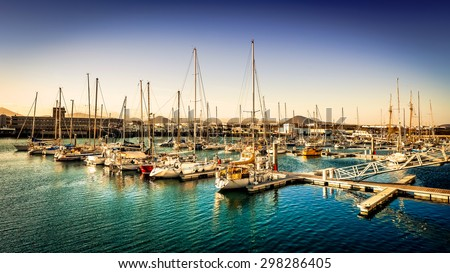 yachts in bay near a city in evening - stock photo