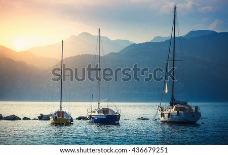 Yachts. Landscape panorama, sailer boats ships sailing lake or sea waves, evening sunset sun sunbeams. Sport yachting or fishing. High mountains background. Malcesine, Garda Lake, Veneto region, Italy - stock photo