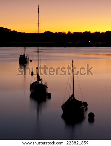 Yachts moored at sunset off the coast of Plymouth in Devon - England. - stock photo