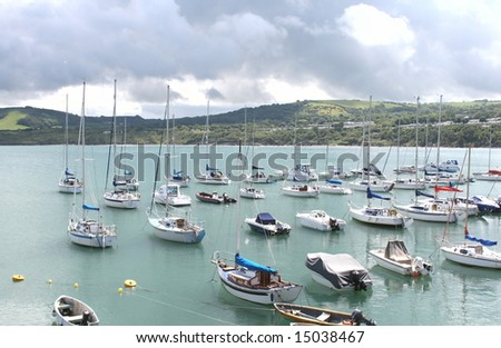 yachts moored in ros looking out to sea with hills in background