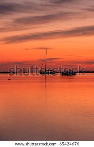 Yachts near the Tavolara island on the golden sunrise over the sea - Sardinia - Italy - stock photo
