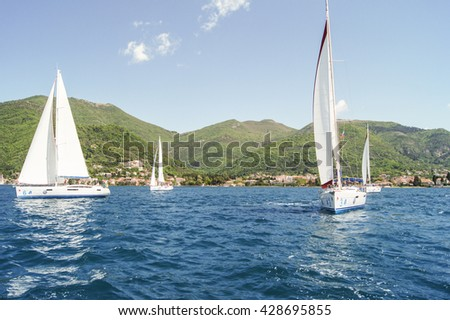 """Yachts on the background of green mountains. Tivat, Montenegro - 26 April, 2016. Regatta """"Russian stream"""" in God-Katorskaya bay of the Adriatic Sea off the coast of Montenegro. - stock photo"""